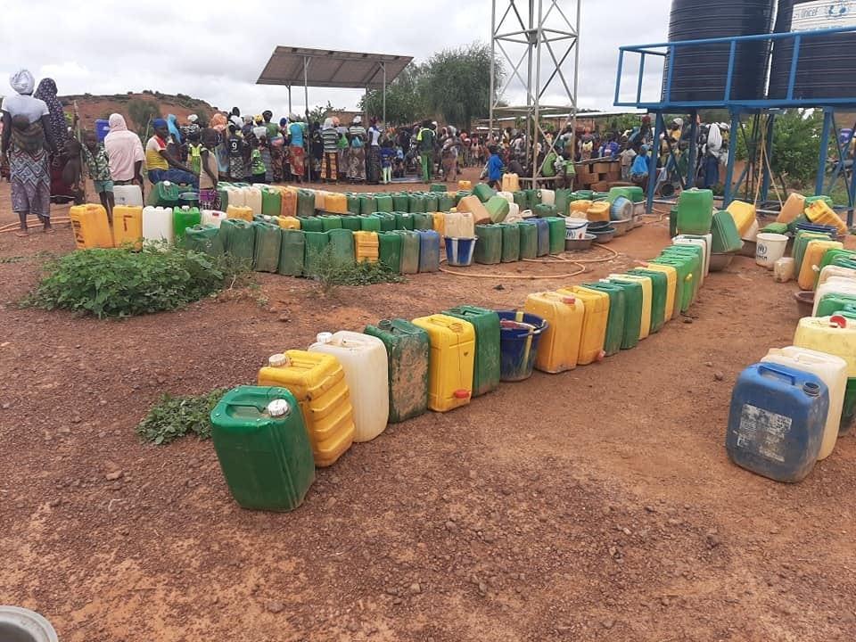 Blocs de latrines et file d'attente à la borne fontaine sur un des sites de déplacés internes à Kaya en août 2020. Crédit photo : Bassératou Kindo